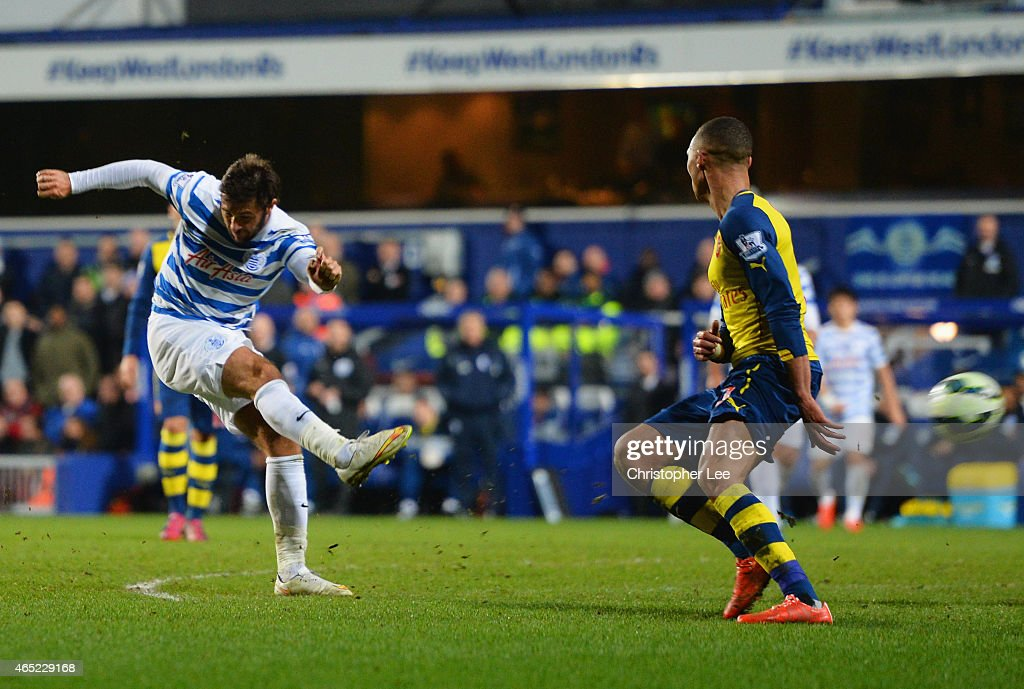Charlie Austin of QPR shoots past Kieran Gibbs of Arsenal to score their first goal during the Barclays Premier League match between Queens Park Rangers and Arsenal at Loftus Road on March 4, 2015 in London, England.