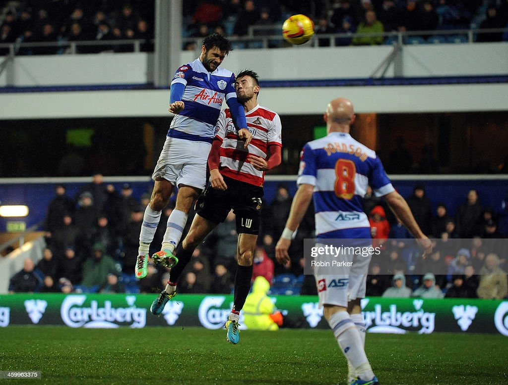 Charlie Austin of Queens Park Rangers scores his team's 2nd goal as he's challenged by Liam Wakefield Doncaster Rovers during the Sky Bet Championship match between Queens Park Rangers and Doncaster Rovers at Loftus Road on January 1, 2014 in London, England,