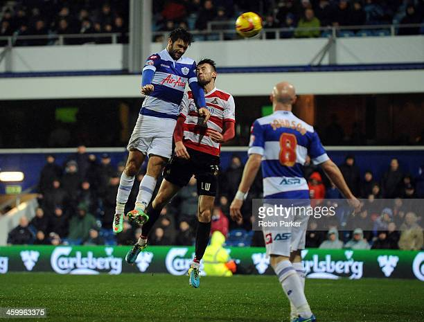 Charlie Austin of Queens Park Rangers scores his team's 2nd goal as he's challenged by Liam Wakefield Doncaster Rovers during the Sky Bet...