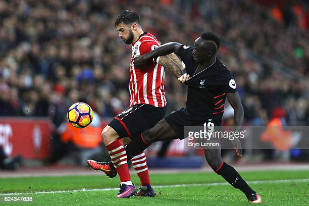 Charlie Austin of Southampton and Sadio Mane of Liverpool battle for possession during the Premier League match between Southampton and Liverpool at...