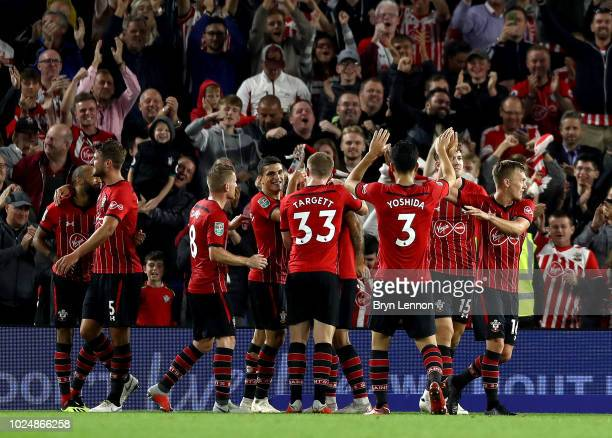 Charlie Austin of Southampton celebrates with teammates after scoring his team's first goal during the Carabao Cup Second Round match between...