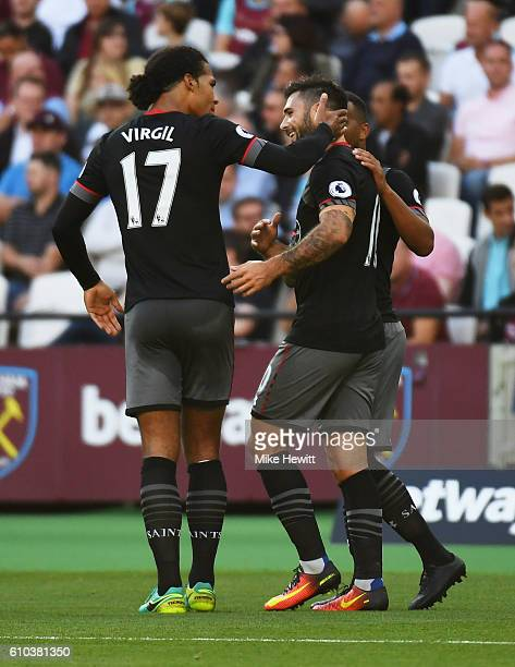 Charlie Austin of Southampton celebrates with Virgil van Dijk as he scores their first goal during the Premier League match between West Ham United...