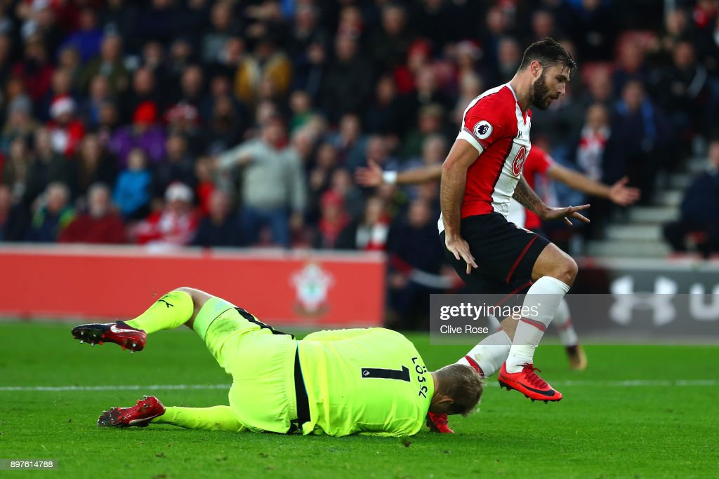 Charlie Austin of Southampton clashes with Jonas Lossl of Huddersfield Town during the Premier League match between Southampton and Huddersfield Town at St Mary's Stadium on December 23, 2017 in Southampton, England.