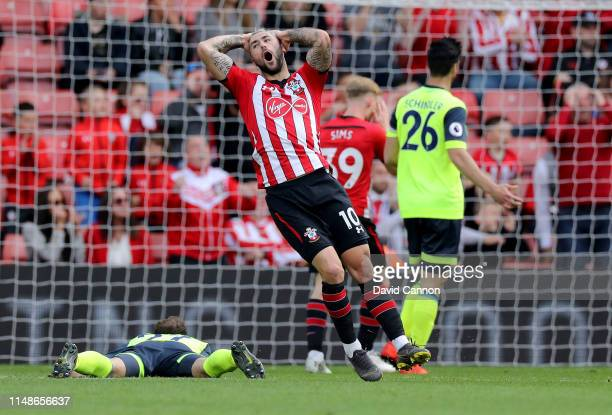 Charlie Austin of Southampton reacts after just missing a goal in the last few minutes as Christopher Schindler of Huddersfield Town looks on during...