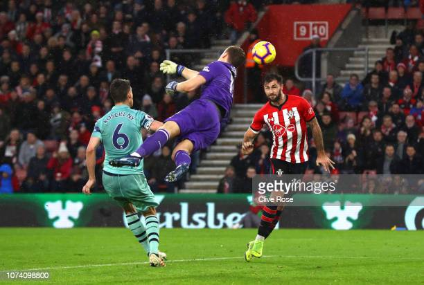 Charlie Austin of Southampton scores his team's third goal as Bernd Leno of Arsenal reaches for the ball during the Premier League match between...