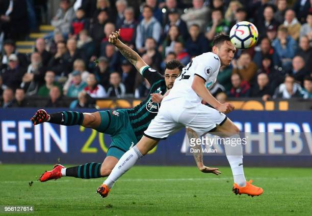 Charlie Austin of Southampton takes a shot on goal under pressure from Connor Roberts of Swansea City during the Premier League match between Swansea...