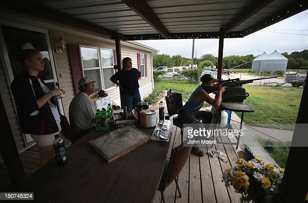 Charlie Becker shoots birds with an air rifle while spending an afternoon on the front porch with his family on August 25 2012 in Logan Kansas Like...