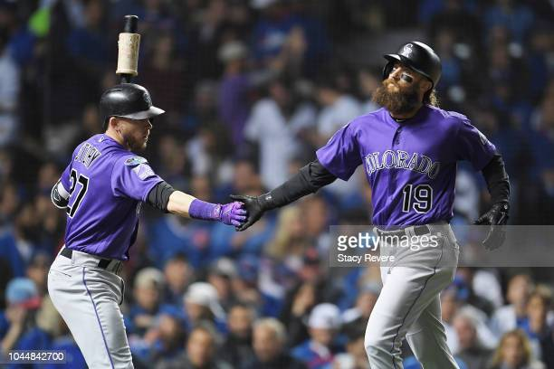 Charlie Blackmon celebrates with Trevor Story of the Colorado Rockies after scoring a run in the first inning against the Chicago Cubs during the...