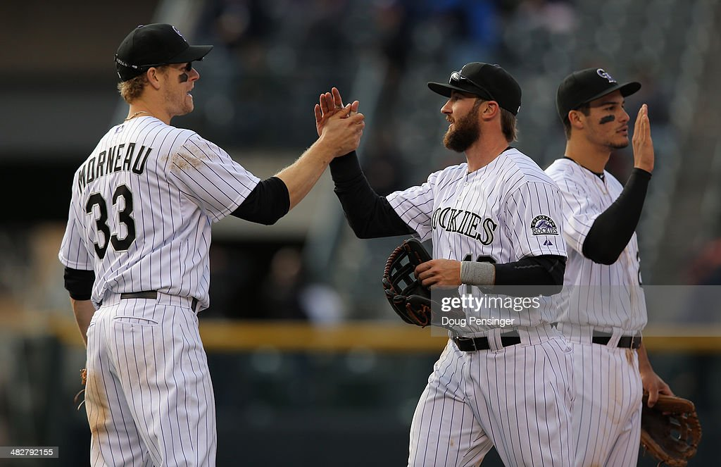 Charlie Blackmon #19 of the Colorado Rockies celebrates with teammates Justin Morneau #33 and Nolan Arenado #28 after they defeated the Arizona Diamondbacks during the home opener at Coors Field on April 4, 2014 in Denver, Colorado. Blackmon went 6 for 6 as the Rockies defeated the Diamondbacks 12-2.