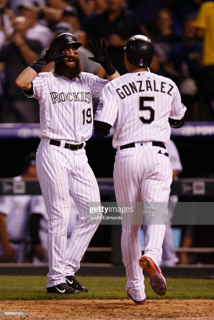 Charlie Blackmon #19 of the Colorado Rockies congratulates Carlos Gonzalez #5 on his three-run home run off of Daniel Descalso of the Arizona Diamondbacks during the fourth inning at Coors Field on July 11, 2018 in Denver, Colorado.