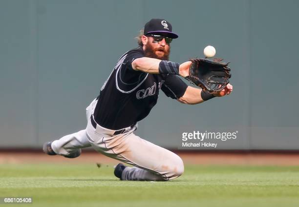 Charlie Blackmon of the Colorado Rockies dives for the ball to make the out on Eugenio Suarez of the Cincinnati Reds in the sixth inning at Great...