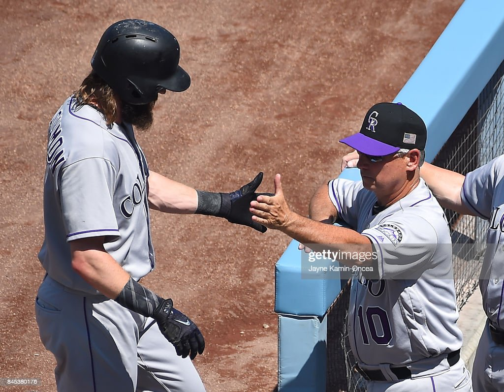 Charlie Blackmon #19 of the Colorado Rockies gets a hand shake from manager Bud Black #10 of the Colorado Rockies after scoring a run in the first inning of the game against the Los Angeles Dodgers at Dodger Stadium on September 10, 2017 in Los Angeles, California.