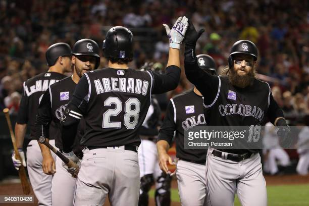 Charlie Blackmon of the Colorado Rockies high fives Nolan Arenado after hitting a threerun home run against the Arizona Diamondbacks during the...