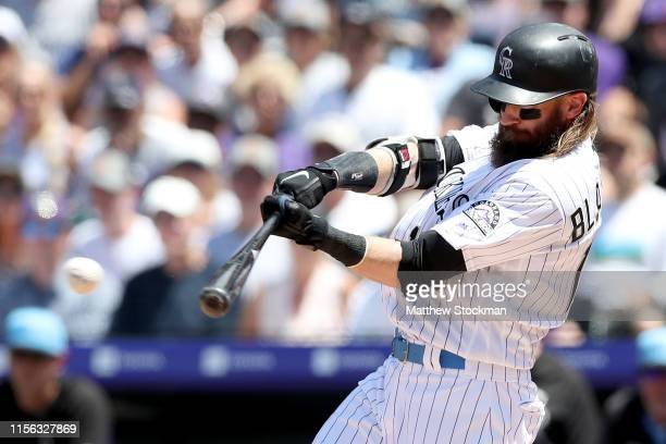 Charlie Blackmon of the Colorado Rockies hits a single in his second at bat in the first inning against the San Diego Padres at Coors Field on June...
