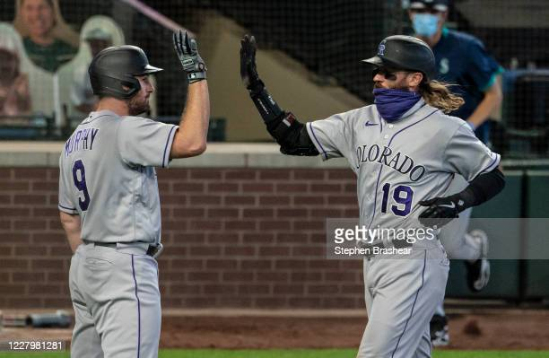 Charlie Blackmon of the Colorado Rockies is congratulated by Daniel Murphy after scoring a run on a single by David Dahl off relief pitcher Taylor...