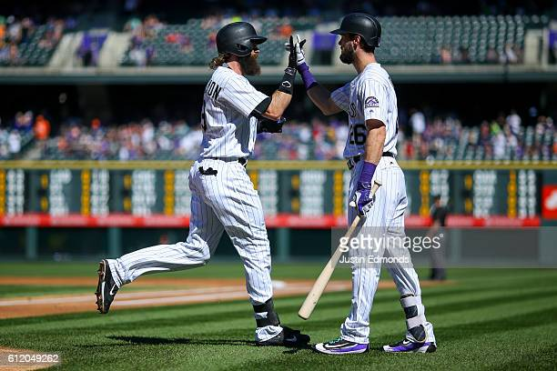 Charlie Blackmon of the Colorado Rockies is congratulated by David Dahl after hitting a solo home run during the first inning against the Milwaukee...