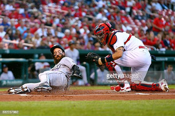 Charlie Blackmon of the Colorado Rockies is tagged out at home plate by Yadier Molina of the St Louis Cardinals in the first inning at Busch Stadium...