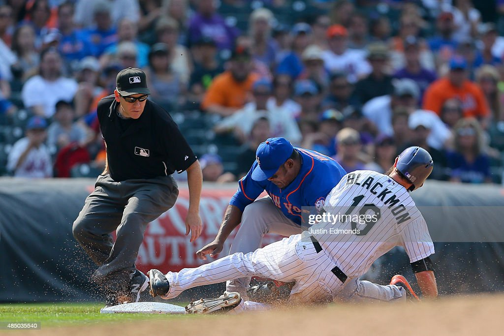 Charlie Blackmon #19 of the Colorado Rockies is tagged out by third baseman Juan Uribe #2 of the New York Mets for the third out of the sixth inning as third base umpire Paul Schrieber looks on at Coors Field on August 23, 2015 in Denver, Colorado. The Mets defeated the Rockies 5-1 to sweep the three game series.