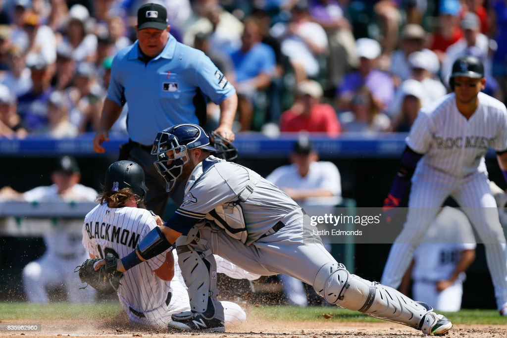 Charlie Blackmon #19 of the Colorado Rockies slides in to score ahead of the tag by Manny Pina #9 of the Milwaukee Brewers as home plate umpire Sam Holbrook looks on during the first inning at Coors Field on August 20, 2017 in Denver, Colorado.