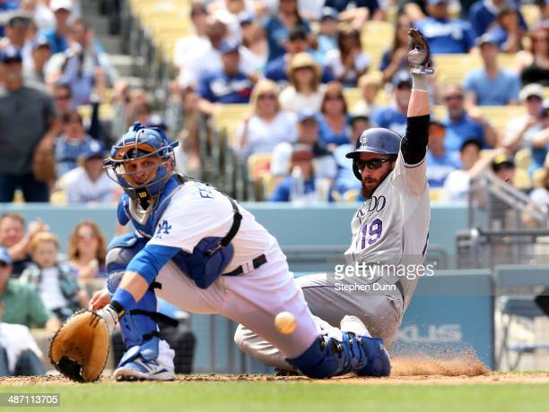 Charlie Blackmon of the Colorado Rockies slides past catcher Tim Federowicz of the Los Angeles Dodgers to score a run from third base after Rockies...