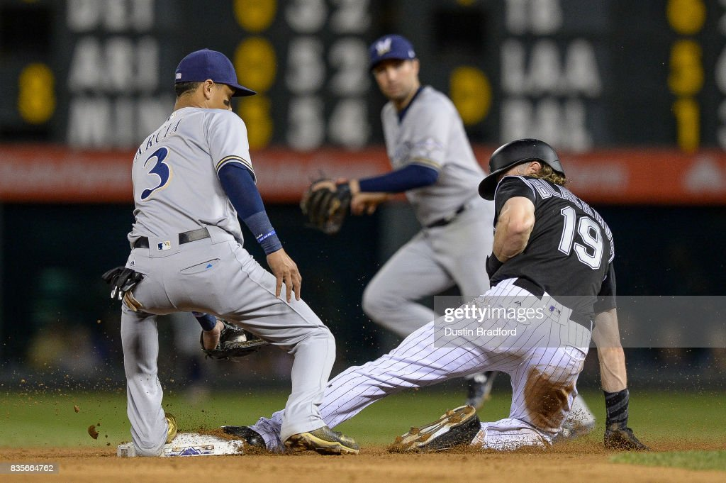 Charlie Blackmon #19 of the Colorado Rockies slides safely into second base ahead of a tag by Orlando Arcia #3 of the Milwaukee Brewers in the seventh inning of a game at Coors Field on August 19, 2017 in Denver, Colorado.