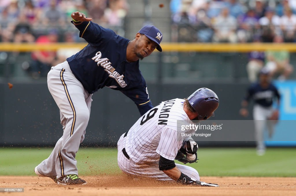 Charlie Blackmon #19 of the Colorado Rockies steals second base as shortstop Jean Segura #9 of the Milwaukee Brewers looses the ball while making the tag in the first inning at Coors Field on June 22, 2014 in Denver, Colorado.