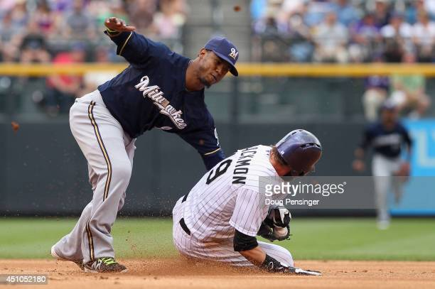 Charlie Blackmon of the Colorado Rockies steals second base as shortstop Jean Segura of the Milwaukee Brewers looses the ball while making the tag in...