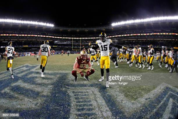 Charlie Callinan of the Boston College Eagles reacts as Joshua Jackson of the Iowa Hawkeyes celebrates after the New Era Pinstripe Bowl at Yankee...