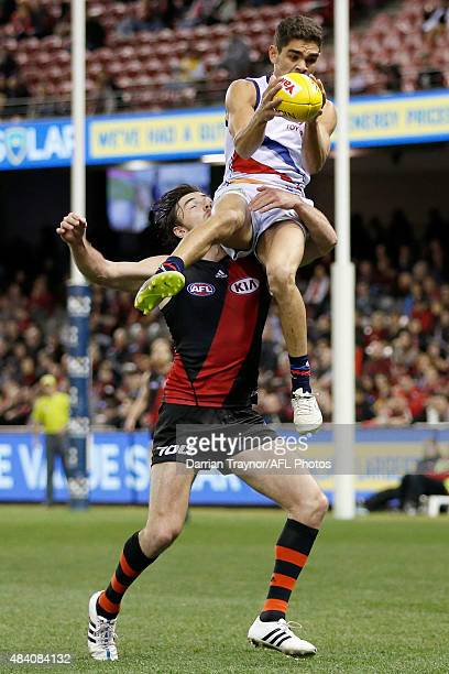 Charlie Cameron of the Crows gathers the ball as Michael Hibberd of the Bombers lays a tackle during the round 20 AFL match between the Essendon...