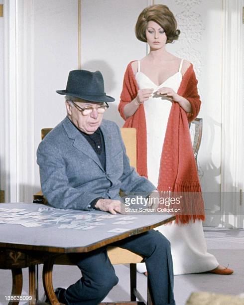 Charlie Chaplin British actor sitting at a table with playing cards strewn across the table top and Sophia Loren Italian actress dressed in a white...