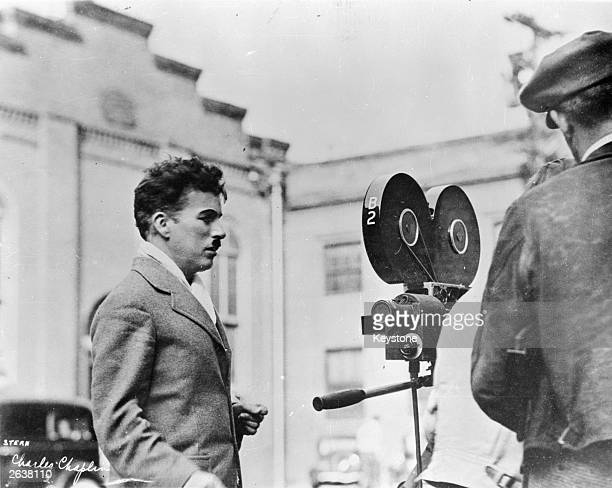 Charlie Chaplin English film actor and director looking at a movie camera Original Publication People Disc HW0505
