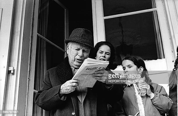 Charlie Chaplin lit le journal sur le perron aux côtés de son épouse Oona et de leur fille Geraldine au Manoir de Ban à CorsiersurVevey Suisse