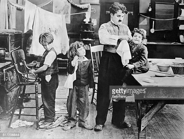 Charlie Chaplin on the set with three small children in a scene eventually cut from his 1918 film 'Shoulder Arms' From left to right the children are...