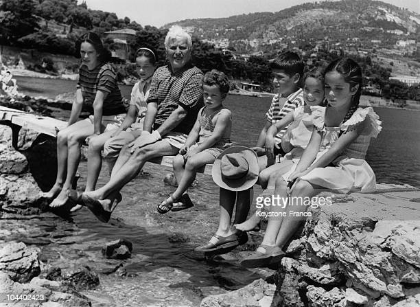 Charlie CHAPLIN seated on water's edge with his family in SaintJeanCapFerrat near Nice From left to right Oona CHAPLIN his wife and their children...