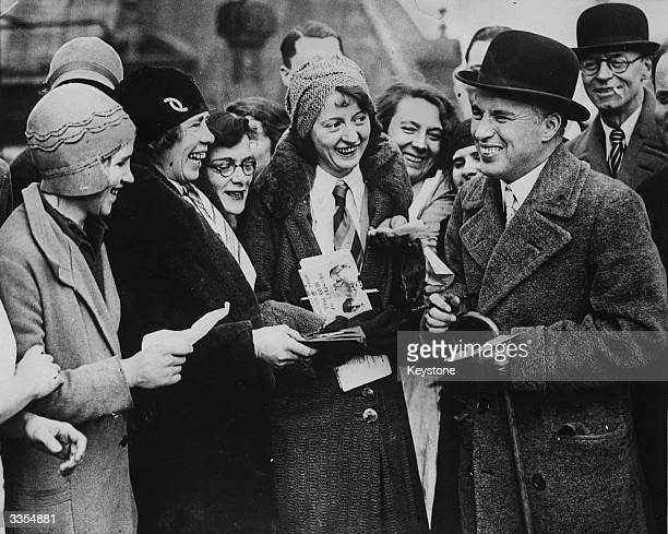 Charlie Chaplin signing autographs for the staff of the hotel where he is staying in London.