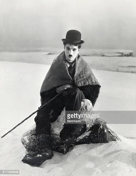 Charlie Chaplin sits wrapped in a blanket in the snow as The Lone Prospector in his 1925 film The Gold Rush