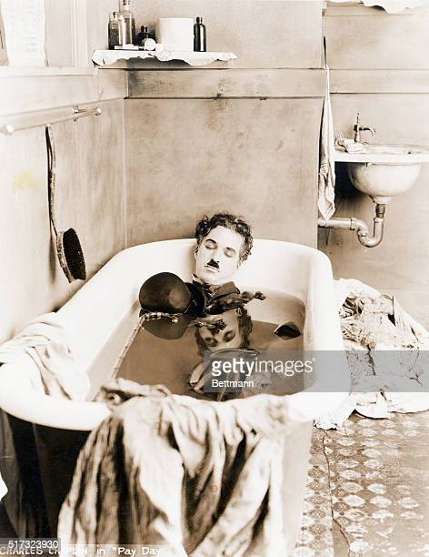 Charlie Chaplin sleeps in a bathtub in a scene from his 1922 film Pay Day