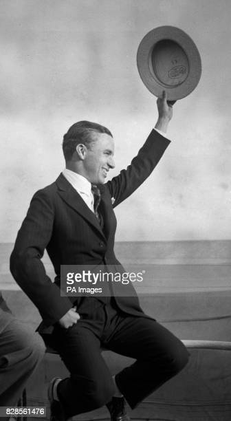 Charlie Chaplin waves his hat onboard the RMS Olympic as it nears Southampton