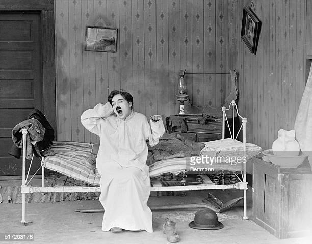 Charlie Chaplin yawns in his highrobe in a scene from his 1919 film Sunnyside