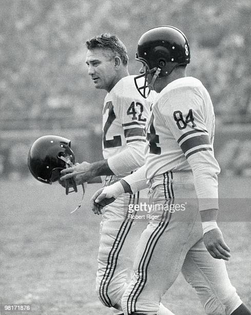 Charlie Conerly and Harland Svare of the New York Giants walk on the field during a circa 1950s game