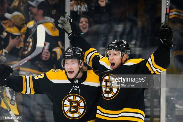 Charlie Coyle and Danton Heinen of the Boston Bruins celebrates with teammates after Coyle scored in overtime to beat the Columbus Blue Jackets in...