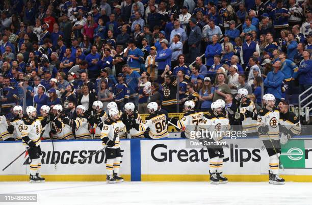 Charlie Coyle Karson Kuhlman Jake DeBrusk and Brandon Carlo of the Boston Bruins skate by the bench to celebrate with teammates after Carlo's goal...