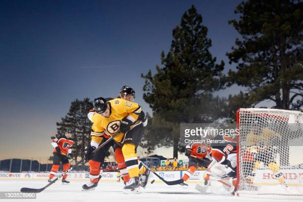 Charlie Coyle of the Boston Bruins attempts to play the puck in front of goaltender Carter Hart of the Philadelphia Flyers during the 'NHL Outdoors...