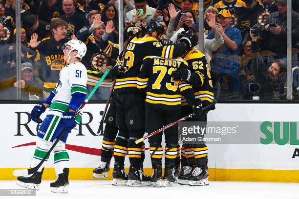 Charlie Coyle of the Boston Bruins celebrates with teammates after scoring in the first period of a game as Troy Stecher of the Vancouver Canucks...