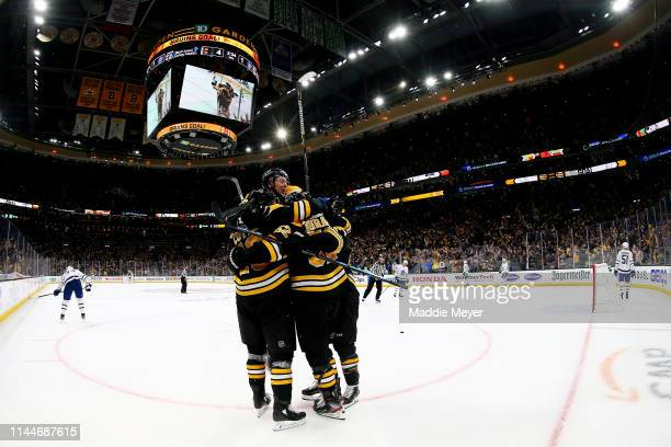 Charlie Coyle of the Boston Bruins left celebrates with Charlie McAvoy and Sean Kuraly after scoring a goal against the Toronto Maple Leafs during...