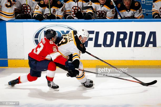 Charlie Coyle of the Boston Bruins skates with the puck against Evgeni Dadonov of the Florida Panthers at the BBT Center on March 23 2019 in Sunrise...