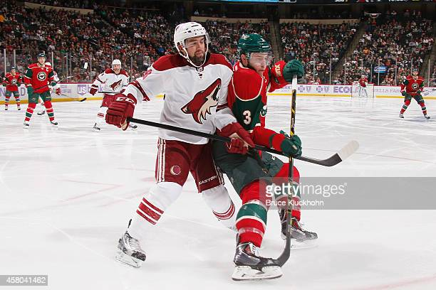 Charlie Coyle of the Minnesota Wild and David Schlemko of the Arizona Coyotes skate to the puck during the game on October 23 2014 at the Xcel Energy...