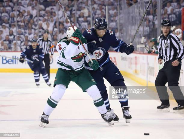 Charlie Coyle of the Minnesota Wild and Joel Armia of the Winnipeg Jets battle for position as they chase the loose puck during third period action...