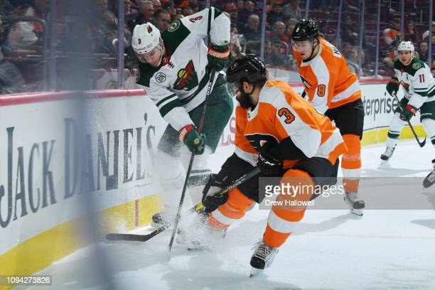 Charlie Coyle of the Minnesota Wild and Radko Gudas of the Philadelphia Flyers scrum in the corner for the puck at Wells Fargo Center on January 14...