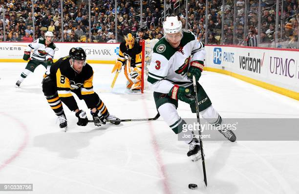 Charlie Coyle of the Minnesota Wild handles the puck against Brian Dumoulin of the Pittsburgh Penguins at PPG Paints Arena on January 25 2018 in...